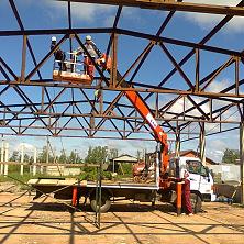 Автоманипулятор работает на строительстве - монтаж металлоконструкций