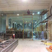 Рабочие на лесах выполняют отделочные работы на реконструируемом складе