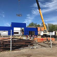 Идет установка стен гаражных боксов из сэндвич-панелей. На монтаже работает 25-тонный автокран