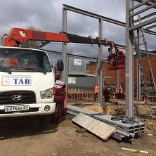 На строительстве гаражей для спецтехники с помощью автовышки ведется монтаж металлических контрукций