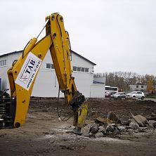 Экскаватор с гидромолотом работает на строительстве станции техобслуживния