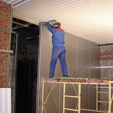 Работы по внутренней отделке промышленного здания: идет монтаж стеновых панелей