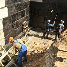 Рабочие производят битумную гидроизоляцию стен