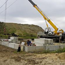 Начало строительства ремонтного цеха. С помощью автокрана идет укладка фундаментных блоков