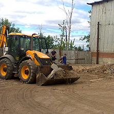 Погрузчик работает на подготовке территории под строительство склада запчастей автомобильной и сельскохозяйственной техники