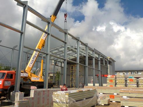 На строительстве склада с помощью автокрана ведется монтаж ограждающих конструкций