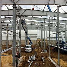 Автовышка Dasan DS-180S и автокран ведут работы по монтажу металлоконструкций на строительстве картофелехранилища