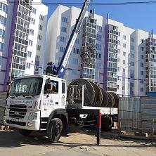 Манипулятор доставляет и разгружает кабельные барабаны на участке строительства жилого дома. Манипулятор Daehan арендован ООО «Старатель»