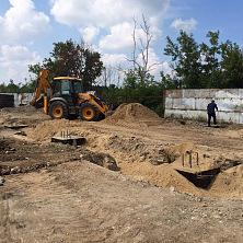 Экскаватор-погрузчик используется во время земляных работ при строительстве склада