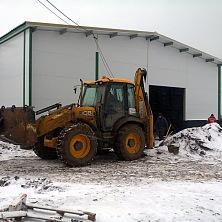 Экскаватор погрузчик на строительстве овощехранилища