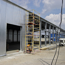 Монтируются стеновые ограждающие конструкции холодного склада из оцинкованного профнастила